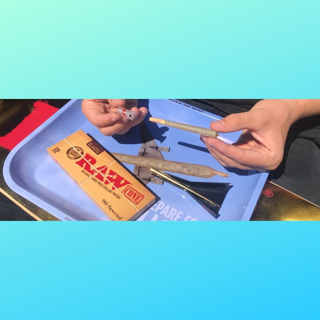 Rolling tray with a hand rolling a joint and blue background